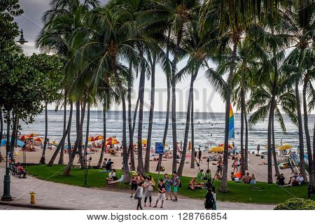 Honolulu, Hawaii, USA - Dec 15, 2015: Waikiki Beach and visitors, near the Kuhio Beach Hula Mound. This area hugely popular with tourists.