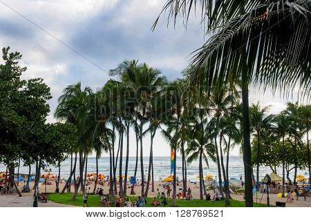 Honolulu, Hawaii, USA - Dec 15, 2015: Waikiki Beach and visitors, near the Kuhio Beach Hula Mound. This image also features a dramatic sky.