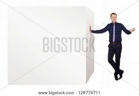 Young businessman stands in free pose and tells about advantages his product, on which he leans, isolated on white background.