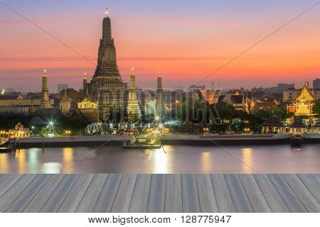 Opening wooden floor, Arun temple Thailand landmark with beautiful sky during sunset