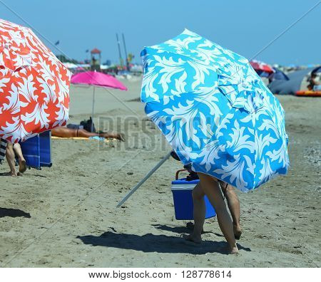 Holiday Makers Move On The Hot Sand With Beach Umbrellas