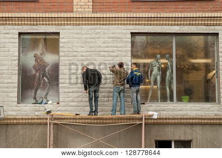 Tyumen, Russia - September 15, 2007: Workers on scaffold install equipment on shop wall with naked mannequins on background