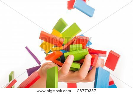 Falling colorful domino onto a hand on white background
