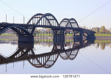 The bridge across the Volga river with reflection in the water in the city of Rybinsk in Russia.