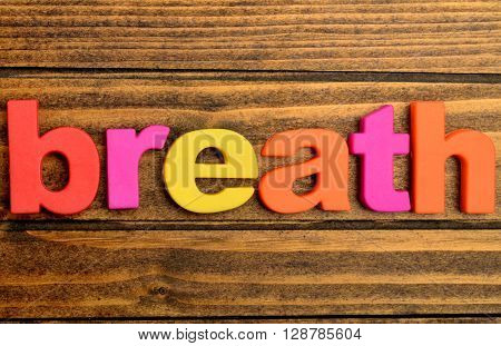 Colorful letters word Breath on wooden table