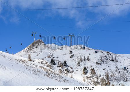 Chair Ski Lift With Skiers Over Blue Sky.  Panorama Of Snow Mountain Range Landscape With Blue Sky,