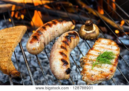 Barbecue grill. Fried sausages. BBQ with fiery sausages on the grill.