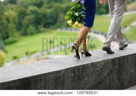 Young man and woman walking on a parapet wall. Yellow roses in hands at the girl. The woman is behind the man. Step by step. Hill the park in the background.