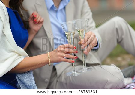 Man and woman with glasses of champagne. Couple with champagne glasses in park. Lovers on picnic.