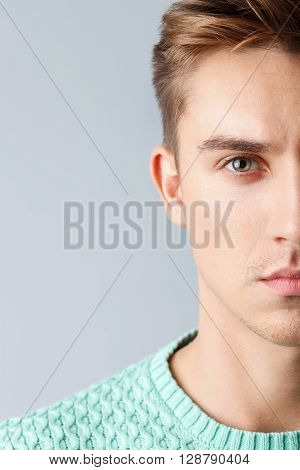 Portrait of half of male face. The serious young man is standing and looking forward with confidence. Isolated and copy space in left side