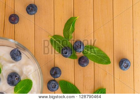 Blueberries with yogurt and mint leafs on wooden table. Blueberries with yogurt and mint in transparent bowl. Transparent bowl with yogurt blueberries and mint. Soft focus. Top or flat view.