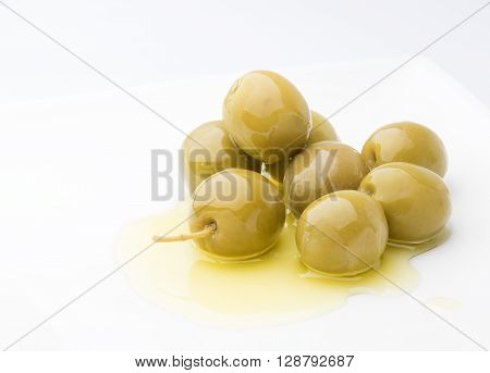 a pile of olives on a pure olive oil extra fine on a white background