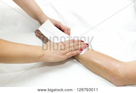 Woman in a beauty salon doing depilation