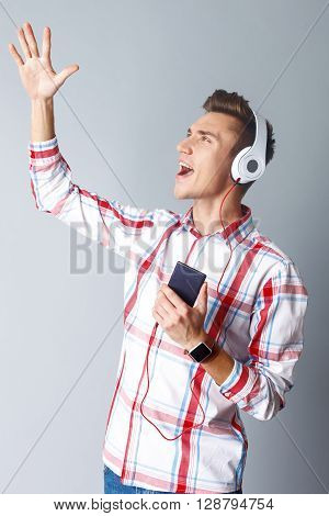 Attractive young man is listening to music from mobile phone. He is singing with passion and gesturing. The student is standing with headphones on ears. Isolated