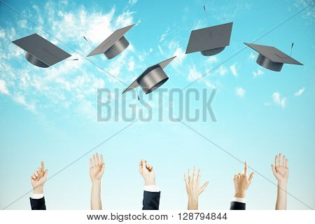 Graduation concept with business people hands throwing up graduation caps on on clear sky background