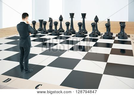 Strategy concept with thinking businessman and black chess pieces standing on huge chessboard with interior in the background. Sideview 3D Rendering