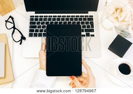 Top view of female hands using pad with blank screen over designer desktop with laptop flowers coffee and other items. Mock up