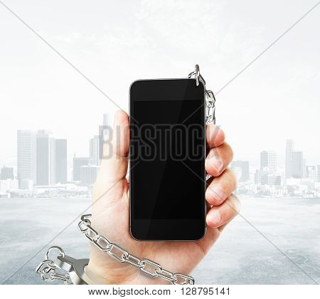 Smartphone with blank screen cuffed to male hand on foggy city background. Concept of social problem. Mock up 3D Rendering