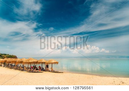 Thatch umbrella sunbeds on a greek beach and clouds reflections in the turquoise waters of the Aegean Sea Nea-Fokea Halkidiki Greece.