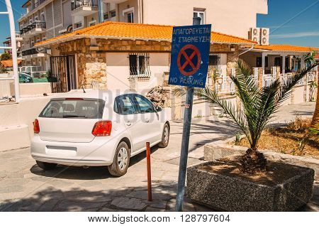 The car is parked under a sign prohibiting parking. In Greece resorts nobody follows the rules of the road.