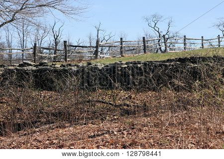 Split rail border fence and stone wall on a sunny day.