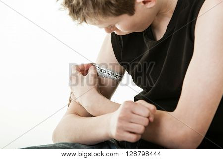 Boy Flexing Bicep And Measuring Arm