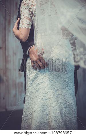 Wedding day. Groom's hand lays on bride's booty