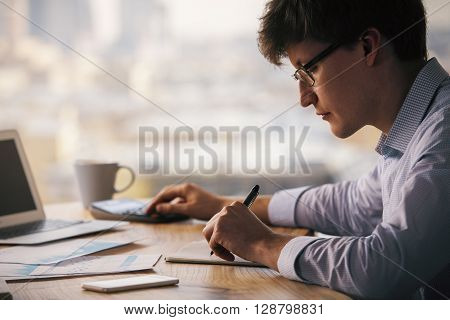 Businessman using calculator and writing in notepad on wooden office desktop with laptop coffee cup smartphone and business reports. Blurry city background