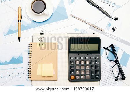Topview of office desktop with business report calculator and other tools