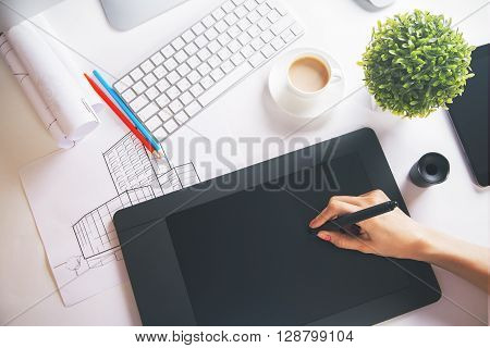 Topview of female hand using graphic tablet on tabletop with building sketch and other items