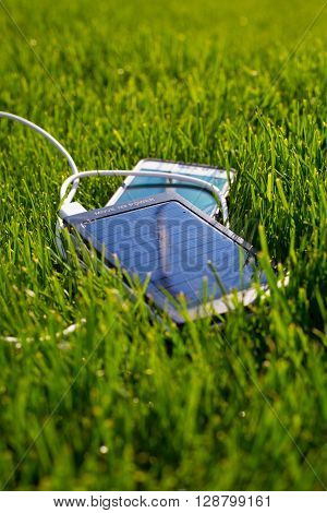 the solar battery on a green grass, for travel, equipment charging.