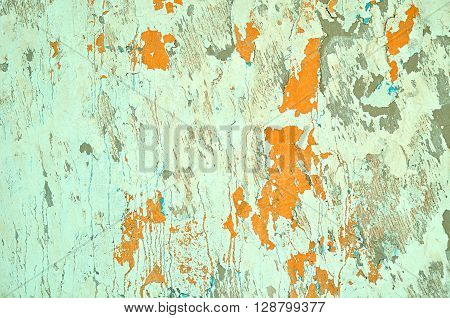 Light green peeling stucco and bright orange peeling paint with turquoise streaks on the old rough wall surface - textured grunge background