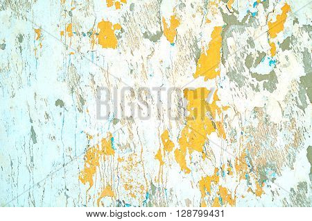 Textured stucco background - light beige peeling stucco and bright orange peeling paint with blue streaks on the aged rough wall surface