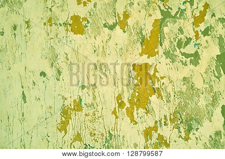 Textured grunge background - peeling dirty green stucco and brown chipped paint with blue streaks on the aged grunge wall surface. Architecture texture background