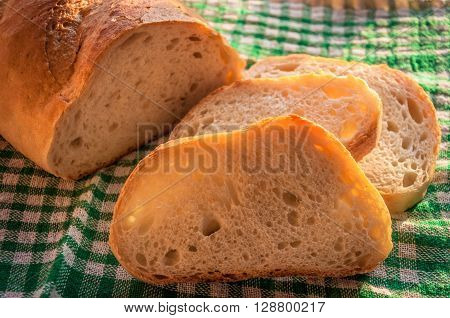 Loaf of Bread, sliced on a checkered tablecloth