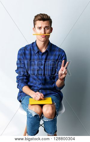 Portrait of cheerful young male student showing peace sign. He is sitting and holding a writing-pad on his knees. The man is keeping pencil on mouth and begging. Isolated