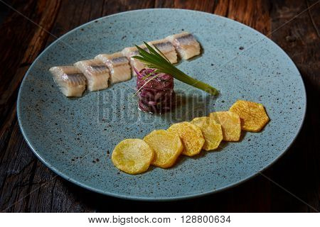 Sliced herring filet with grilled potato and onion