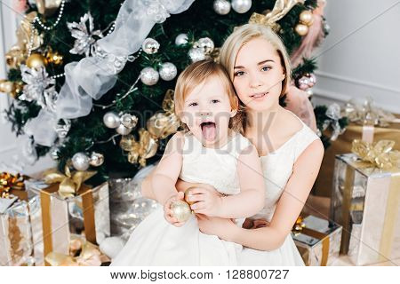 happy family mother and daughter at Christmas and New Year with gifts around the Christmas tree. in Christmas, in identical white dresses, New Year's concert, Merry Christmas, Mom daughter indulges
