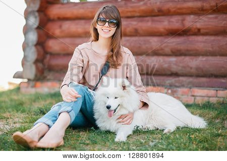 young stylish hipster woman girl playing white kid-skin dog in country side.