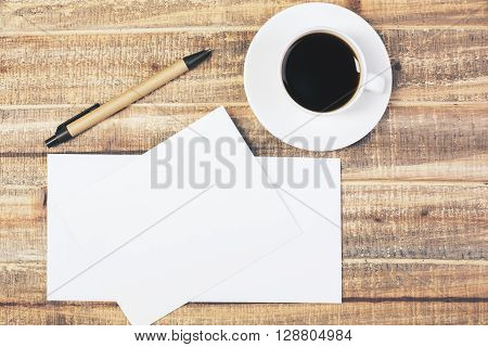 Topview of antique wooden desktop with pen coffee cup and blank envelopes. Mock up
