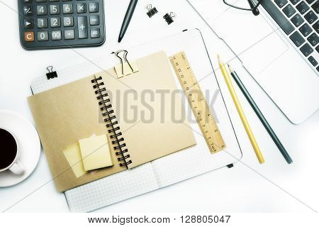 Topview of white desk with brown notepad ruler pencils and other tools