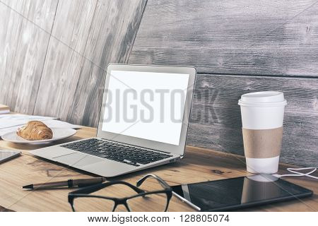 Sideview of wooden desktop with blank white laptop screen croissant tablet and other items. Mock up