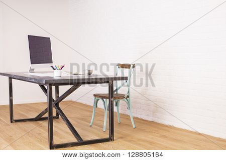 Sideview of desk with computer monitor and an antique chair next to it on wooden floor and white brick background