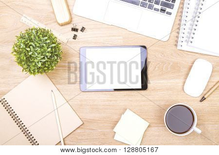 Topview of wooden desk with blank tablet and office tools. Mock up