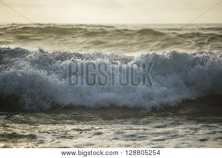 Foamy stormy wave crashing during sunset presenting a dark mood