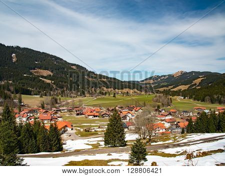 spring scene of mountain village  in a valley with mountain background in the German Alps