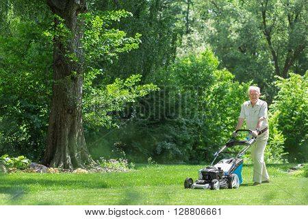 Retired Man Mowing The Grass
