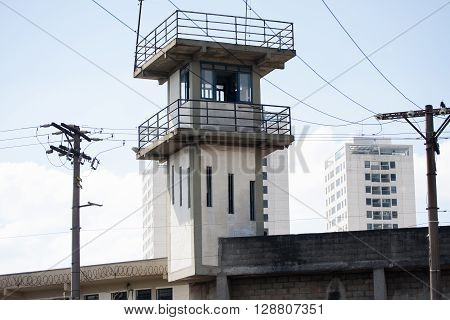 Prison security tower and residential building with blue sky and white clouds behind