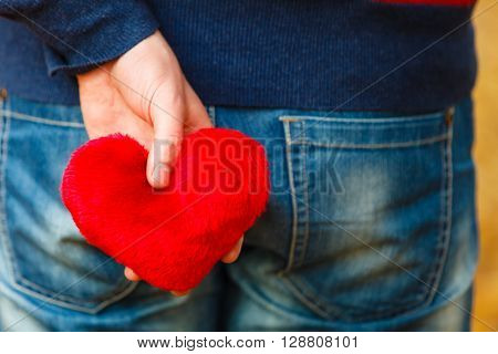 Feelings romance dating relationship concept. Man holding heart behing his body. Young male with love symbol hidden.