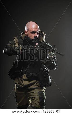 Military war conflict soldiers - Special forces soldier man hold Machine gun on a dark background. Military equipment of Russian soldiers